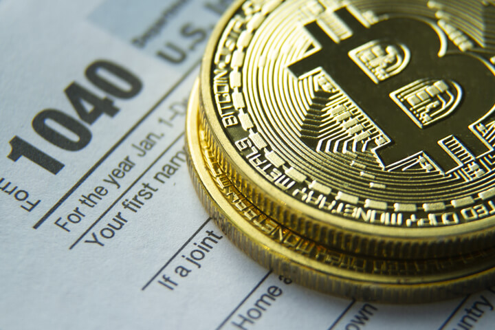 Bitcoins stacked on an IRS 1040 tax form concept image for cryptocurrency tax issues
