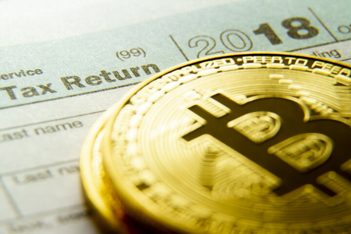 Bitcoins stacked on a 2018 IRS 1040 tax form concept image for cryptocurrency tax issues