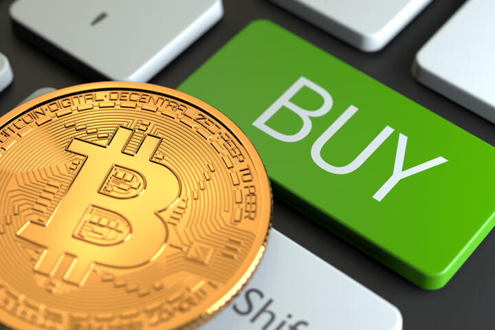 Computer keyboard with green BUY key with Bitcoin overlaying keys concept of market buy bitcoin or cryptocurrency
