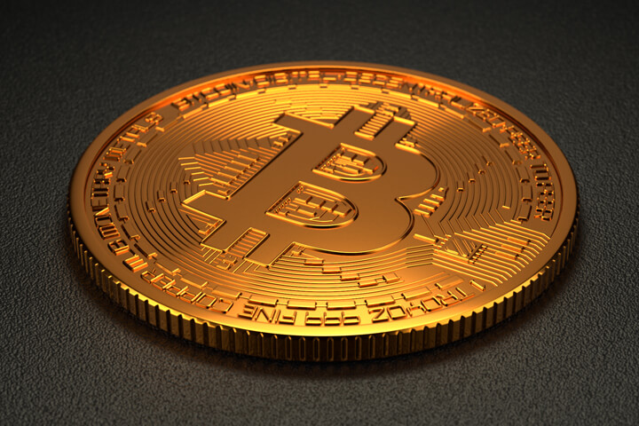 Single Bitcoin on dark background with soft light