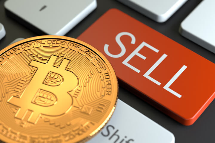 Keyboard with large red SELL key with Bitcoin overlaid on the keys