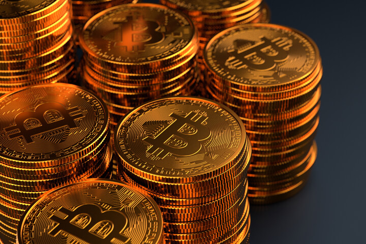 Multiple stacks of Bitcoins on dark background with stacks exiting left side of frame