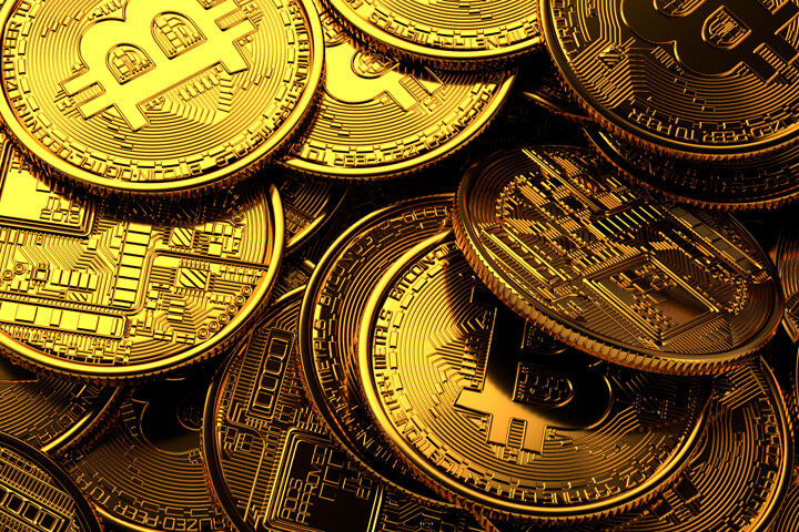 Pile of random Bitcoins with golden lighting