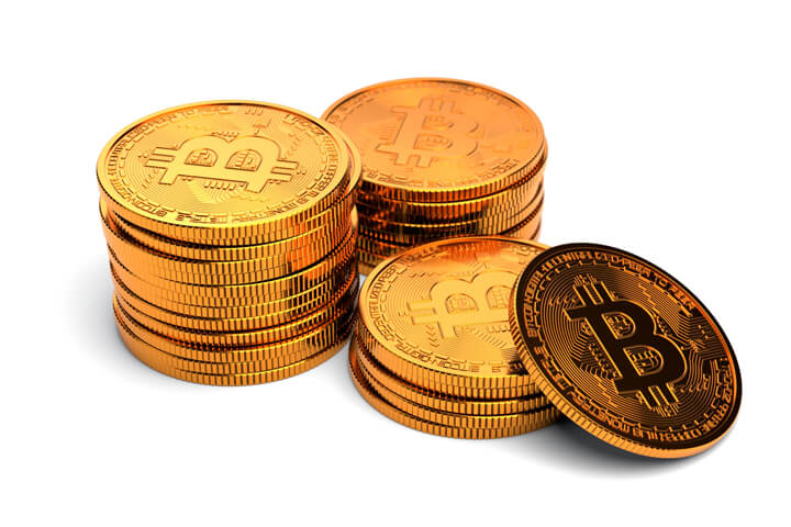 Three small stacks of Bitcoins with one coin leaning against a small stack