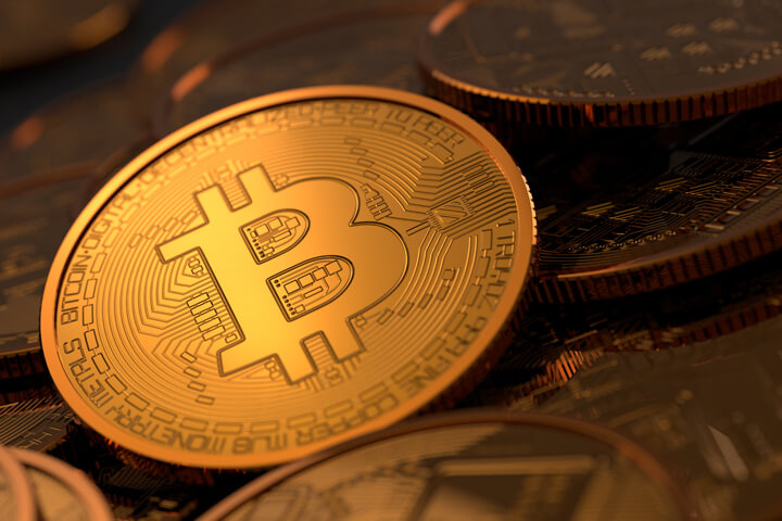 Random assortment of Bitcoins with soft golden light focused on one coin