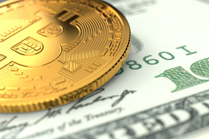 Single Bitcoin laid on U.S. one hundred dollar bill
