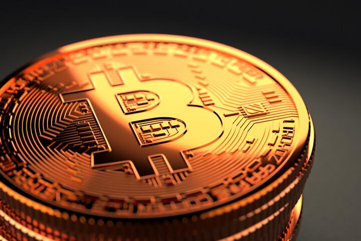 Shiny Bitcoin stack on dark background with sharp golden lighting