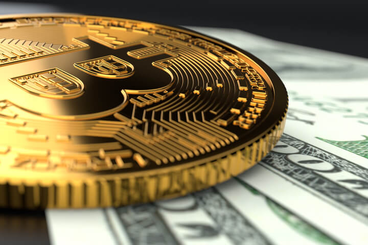 Single Bitcoin close-up photo laying on U.S. currency