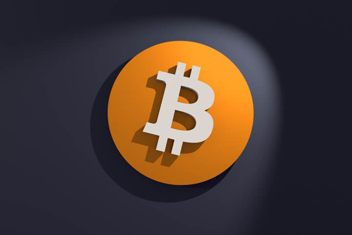Front view of orange and white Bitcoin B logo on dark wall with spotlight