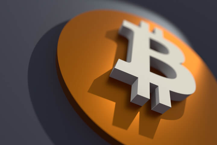 Angled view of orange and white Bitcoin B logo with short depth of field and spotlight