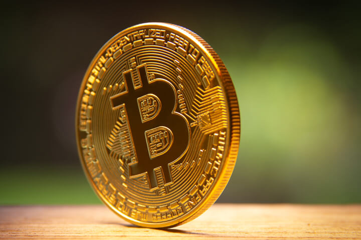 Bitcoin balancing on edge on wood surface with nature background