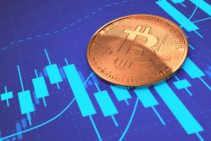Bitcoin laying on blue stock price candlestick chart