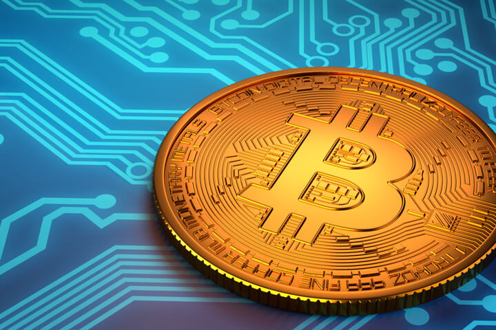 Bitcoin laid on top of blue circuit board representing digital currency or cryptocurrency