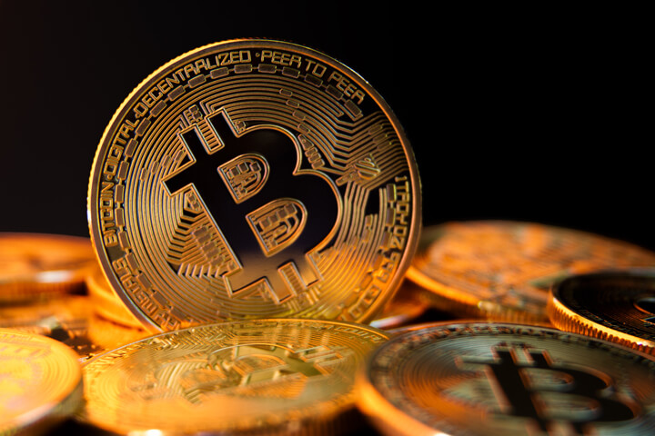 Bitcoin standing on edge in pile of bitcoins with black background