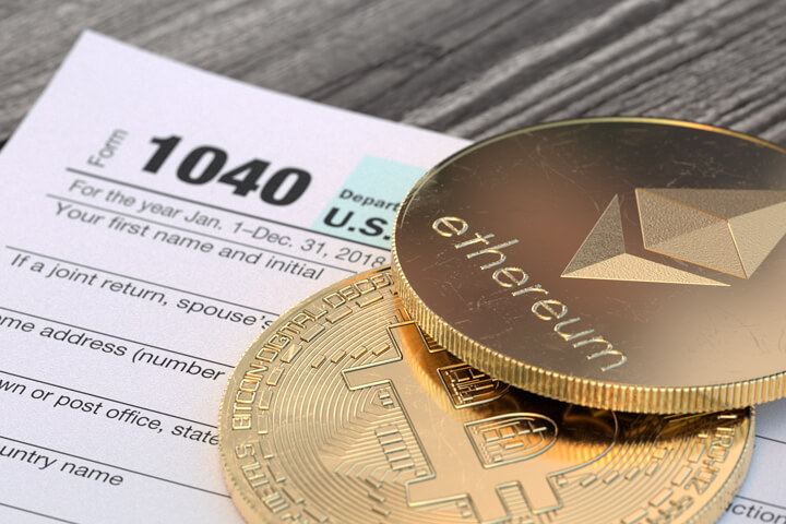 Bitcoin and an Etherum cryptocurrency coins lying on an IRS 1040 tax form concept for cryptocurrency taxes