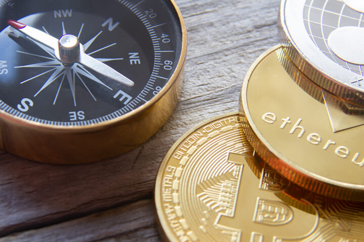 Navigational compass with crypto coins Bitcoin, Ethereum, and Ripple on wood planks