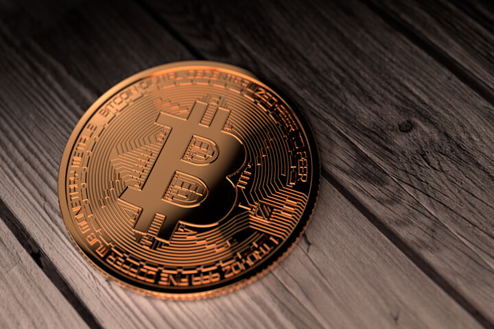 Single Bitcoin placed on weathered boards