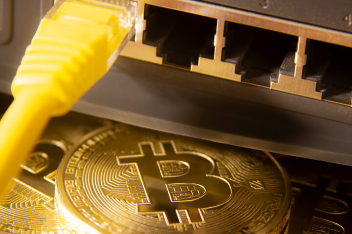Bitcoins with yellow LAN Cat-5 cable and router ports