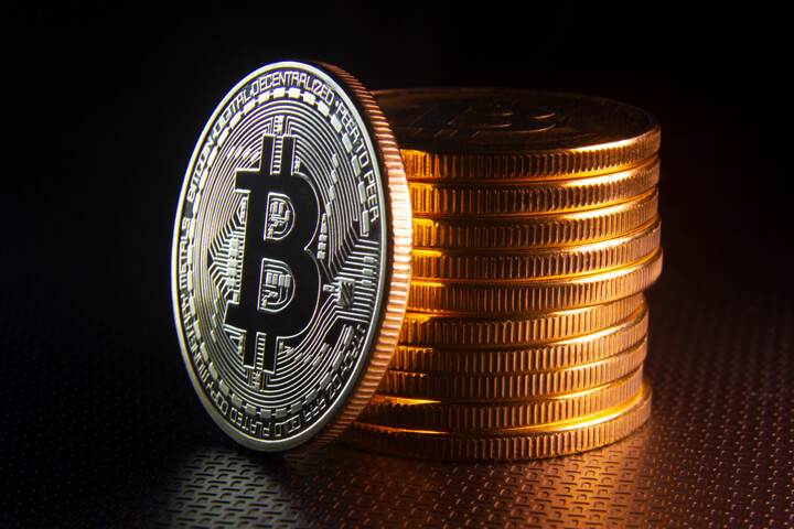 Free photo of a Bitcoin leaning against a stack of Bitcoins dark background
