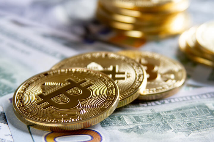 Bitcoins scattered on new U.S. 100 dollar bills