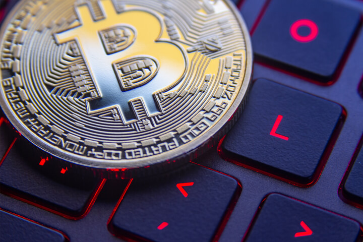 Bitcoin on gamer laptop keyboard with screen back light