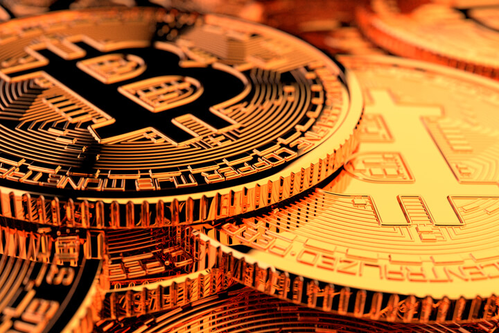 Random pile of Bitcoins with camera positioned low front with hard back lighting