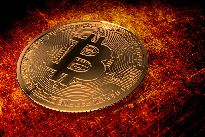 Bitcoin on grunge background lit in orange and red