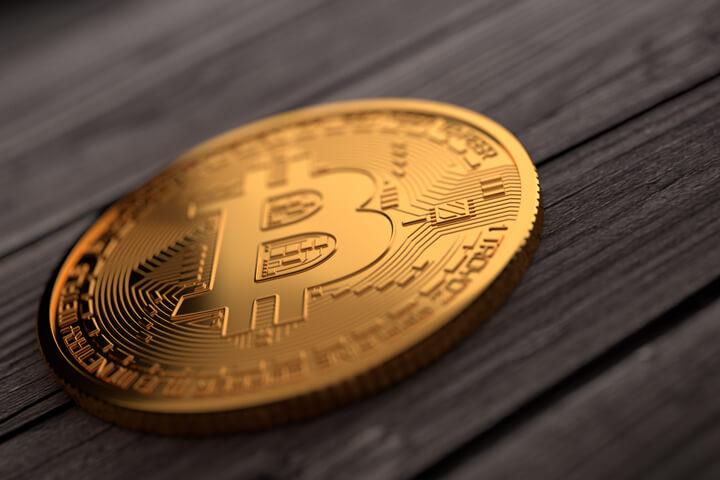 Single gold Bitcoin placed on weathered wood planks with upper right soft light