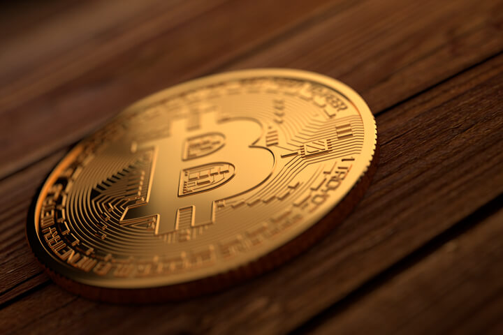 Single gold Bitcoin placed on stained wood planks with upper right soft light