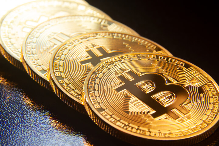 Bitcoins in a row on reflective black textured surface