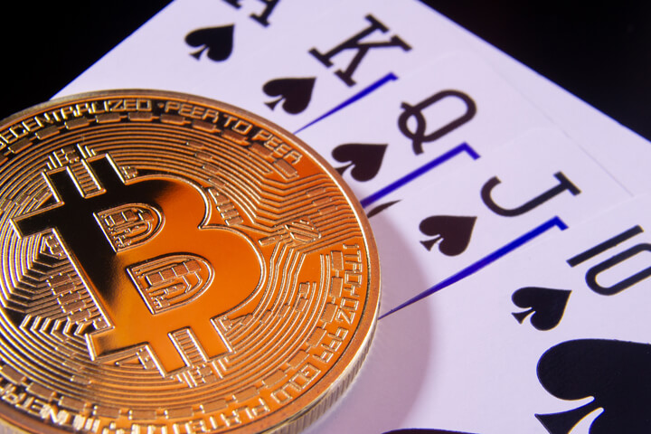 Bitcoin on royal flush card hand in spades gamble concept