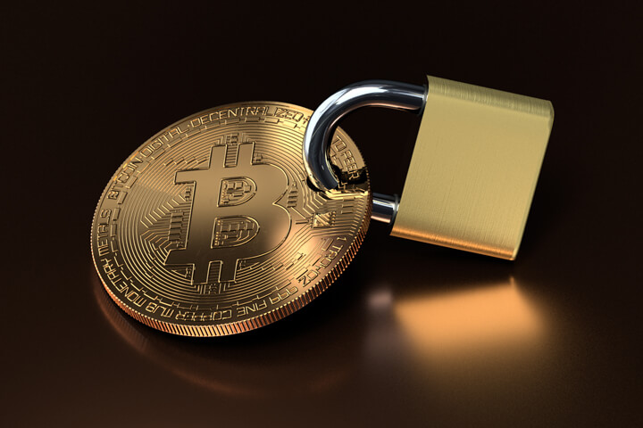 Bitcoin secured with padlock on reflective metallic surface