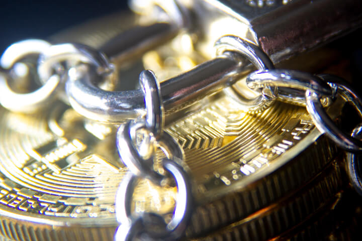 Stack of Bitcoins wrapped with chains and locked with a small padlock