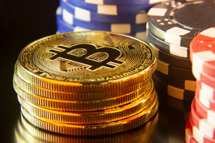 Bitcoins stacked in front of stacks of poker chips with reflection gambling concept