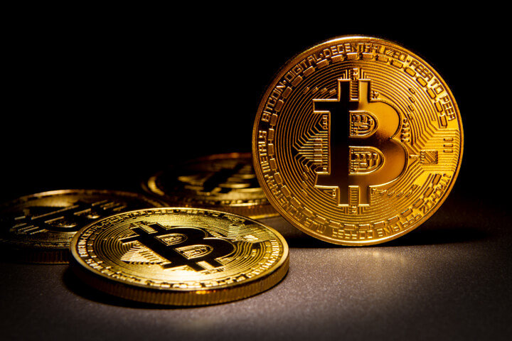 Shiny bitcoin balancing on edge with three other Bitcoins in background