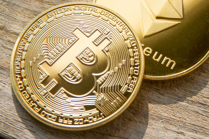 Bitcoin with Ethereum coin on wood background