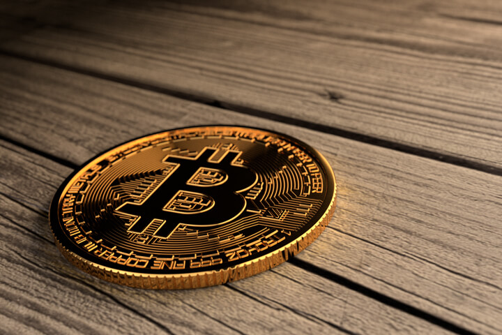 Single Bitcoin lying on old weathered faded wood planks