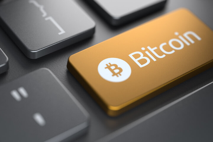 Computer keyboard with orange Bitcoin key highlighted with spot light