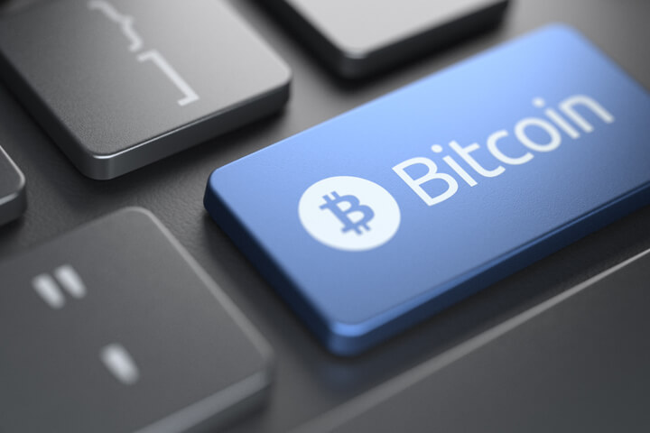 Computer keyboard with blue Bitcoin key highlighted by spotlight from behind