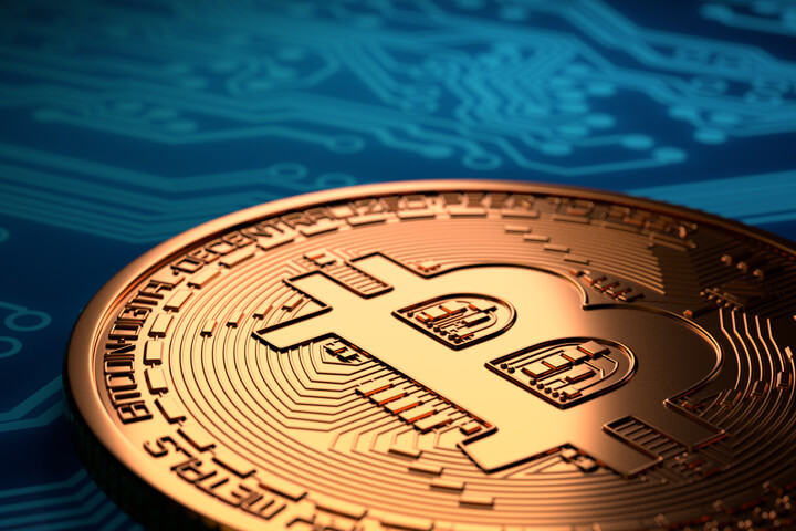 Single Bitcoin with hard spot light laying on blue circuit board