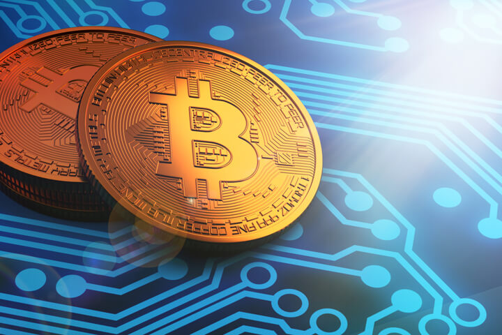 Small stack of Bitcoins on blue circuit board with hard bright corner light
