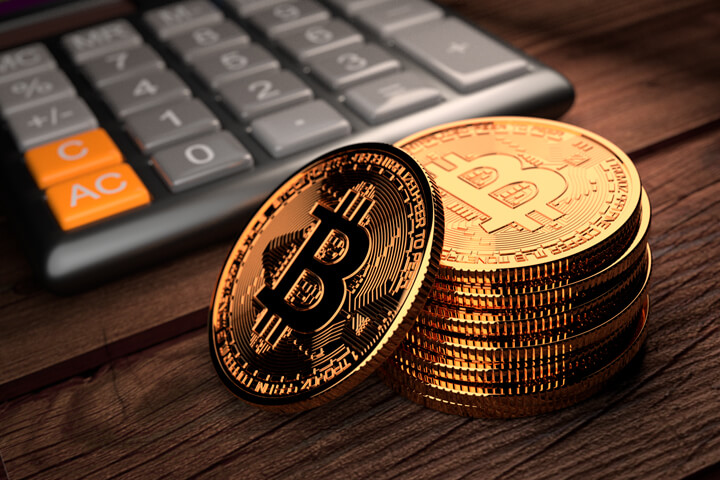 Stack of Bitcoins with one leaning in front of digital calculator