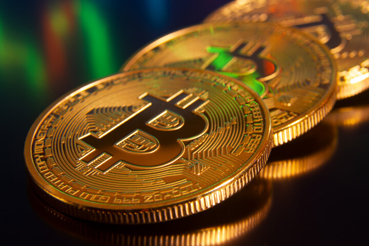 Row of Bitcoins reflecting stock price candlestick chart in background
