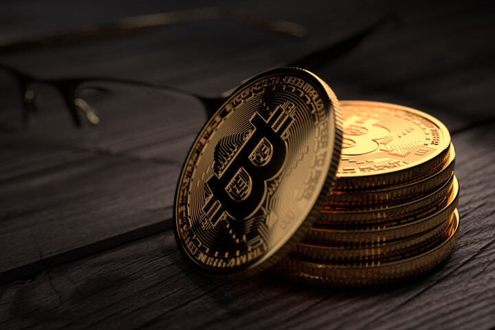 Stack of Bitcoins on rough weathered wood with reading glasses in background