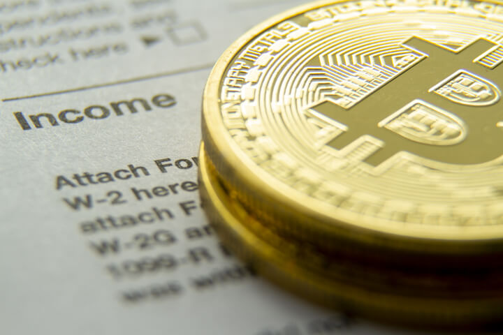 Bitcoins stacked on an IRS 1040 tax form showing the Income information section