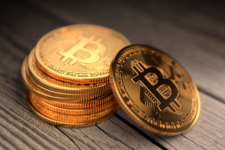 Stack of Bitcoins with one leaning coin on old weathered wood boards