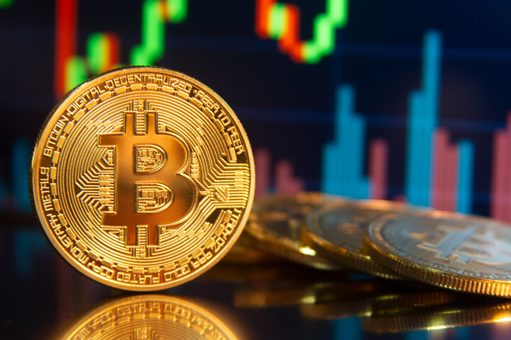 Bitcoin on edge in front of monitor showing BTC candlestick price change and trading volume