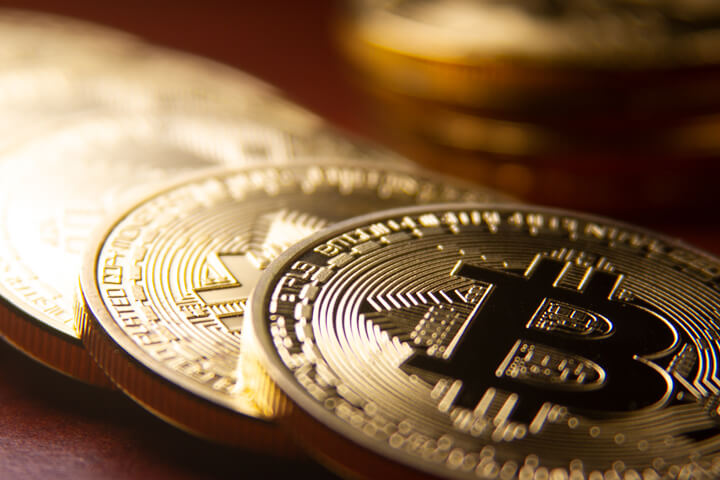 Bitcoins arranged in a row with single coin in background with short depth of field