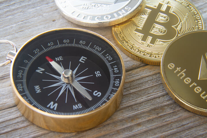 Ethereum coin, Bitcoin, and Litecoin next to navigation compass on wood surface