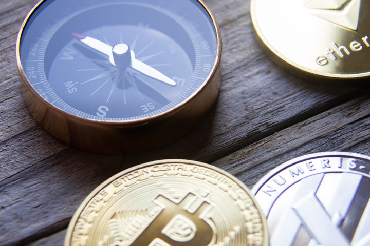 Cryptocurrency coins next to navigation compass